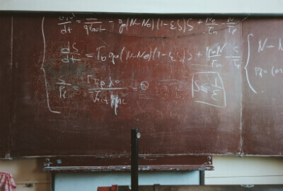 an old used blackboard with formluae written across it