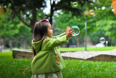child playing catch with bubblesin the park