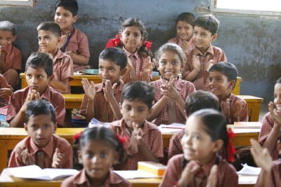 photo showing happy children at their desks in a classroom
